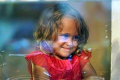 A menina bonita olha na janela de uma loja em OIA, e faz as caras engraçadas fotos de stock royalty free