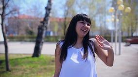 A menina bonita oriental na blusa branca olha a câmera, acenando seus mão e riso vídeos de arquivo