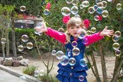 A menina bonita pequena anda com um brinquedo macio em suas mãos no ar livre Menina que joga com bolhas de sabão no jardim fotografia de stock
