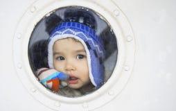 Menina bonita pequena atrás da janela do navio Imagens de Stock