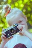 Menina bonita pequena com câmera retro Fotografia de Stock