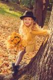 Menina bonita pequena com cabelo louro no fundo do outono imagens de stock