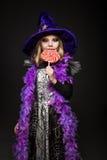 A menina bonita pequena com o traje da bruxa do Dia das Bruxas come doces coloridos imagens de stock