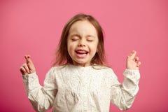 A menina bonita pequena com olhos fechados e os dedos cruzados faz um desejo, expressa a necessidade sincera de cumprir o sonho,  imagem de stock