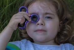 A menina bonita pequena do retrato está jogando o girador azul à disposição Imagem de Stock Royalty Free