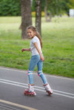 Menina bonita pequena em patins de rolo Imagens de Stock