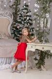 Menina bonita pequena em um vestido de noite vermelho a árvore de Natal Imagens de Stock