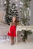 Menina bonita pequena em um vestido de noite vermelho a árvore de Natal Fotos de Stock