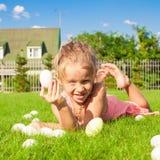 A menina bonita pequena encontra ovos da páscoa no verde Fotografia de Stock