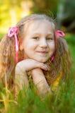A menina bonita pequena encontra-se na grama verde, verão do sol no pa da cidade Fotografia de Stock