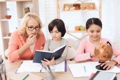 A menina bonita pequena está estudando o globo ao lado da mulher idosa que olha o livro com rapaz pequeno fotografia de stock