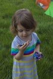 A menina bonita pequena está jogando com os dois giradores nas mãos Imagens de Stock Royalty Free