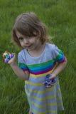 A menina bonita pequena está jogando com os dois giradores nas mãos Imagem de Stock Royalty Free