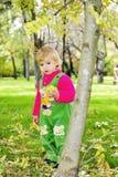 Menina bonita pequena na erva verde em o outono Imagem de Stock Royalty Free