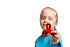 A menina bonita pequena no t-shirt azul está jogando o girador vermelho à disposição Imagens de Stock
