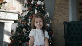 Menina bonita pequena que está perto de uma árvore de Natal e que guarda um presente do Natal na caixa video estoque