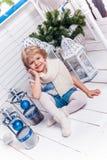 Menina bonita pequena que senta-se ao lado de uma árvore de Natal e de um Christma fotos de stock