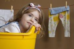 A menina bonita pequena sorri e senta-se em um banho amarelo Uma criança sonha de transformar-se um adulto Imagens de Stock