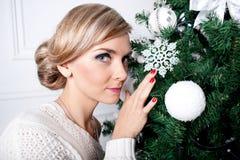 A menina bonita perto de uma árvore do ano novo Foto de Stock