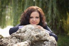 A menina bonita perto de uma pedra grande Fotografia de Stock