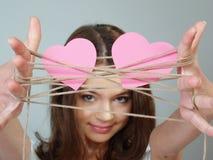 A menina bonita prende dois corações cor-de-rosa em suas mãos Imagem de Stock Royalty Free