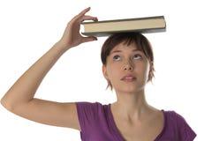 A menina bonita prende o livro em uma cabeça Fotografia de Stock