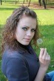 A menina bonita prende um dente-de-leão em uma mão Imagens de Stock Royalty Free