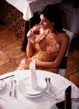 A menina bonita prova o vinho em um restaurante imagem de stock