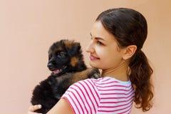 Menina bonita que abraça firmemente seu cachorrinho pequeno bonito imagem de stock