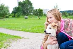 Menina bonita que abraça seu cão Imagem de Stock
