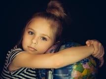 Menina bonita que abraça um globo fotografia de stock royalty free