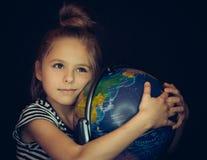 Menina bonita que abraça um globo imagens de stock