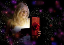 Menina bonita que abre a caixa de presente vermelha do Natal foto de stock