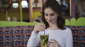 Menina bonita que agita a bebida do gosto com o tubule no café 4K filme