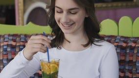 Menina bonita que agita a bebida do gosto com o tubule no café lentamente filme