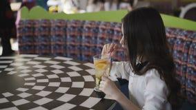 Menina bonita que agita a limonada com o tubule no café video estoque