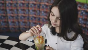 Menina bonita que agita a limonada com tubule e que sorri na câmera no café vídeos de arquivo