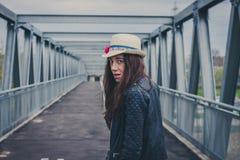 Menina bonita que anda afastado em uma ponte Imagens de Stock Royalty Free