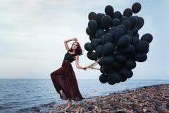 Menina bonita que anda com balões pretos imagens de stock