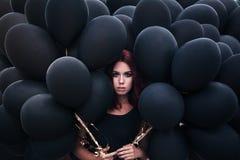 Menina bonita que anda com balões pretos Imagem de Stock Royalty Free