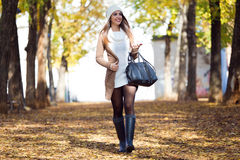 Menina bonita que anda com telefone celular no outono Fotos de Stock