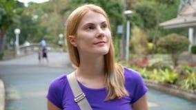 Menina bonita que anda em um parque, sorrindo Tendo uma boa estadia durante férias em um país tropical vídeos de arquivo