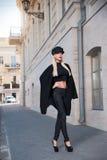 Menina bonita que anda em um revestimento preto fotos de stock royalty free