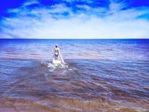 Menina bonita que anda entre a água de brilho do mar azul imagem de stock