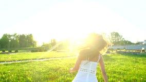Menina bonita que anda tendo o divertimento na grama verde no dia de verão do parque no por do sol do sol Felicidade da saúde da  filme