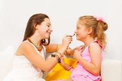 Menina bonita que aplica o batom em seu amigo Fotografia de Stock Royalty Free