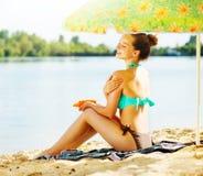 Menina bonita que aplica o creme do bronzeado em sua pele Fotos de Stock Royalty Free