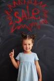 Menina bonita que aponta com seu dedo na inscrição do giz Imagem de Stock
