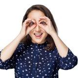 A menina bonita que aponta vidros binoculares dos dedos circunda a felicidade das emoções fotografia de stock royalty free