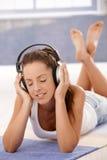 Menina bonita que aprecia a música que coloca no assoalho fotos de stock
